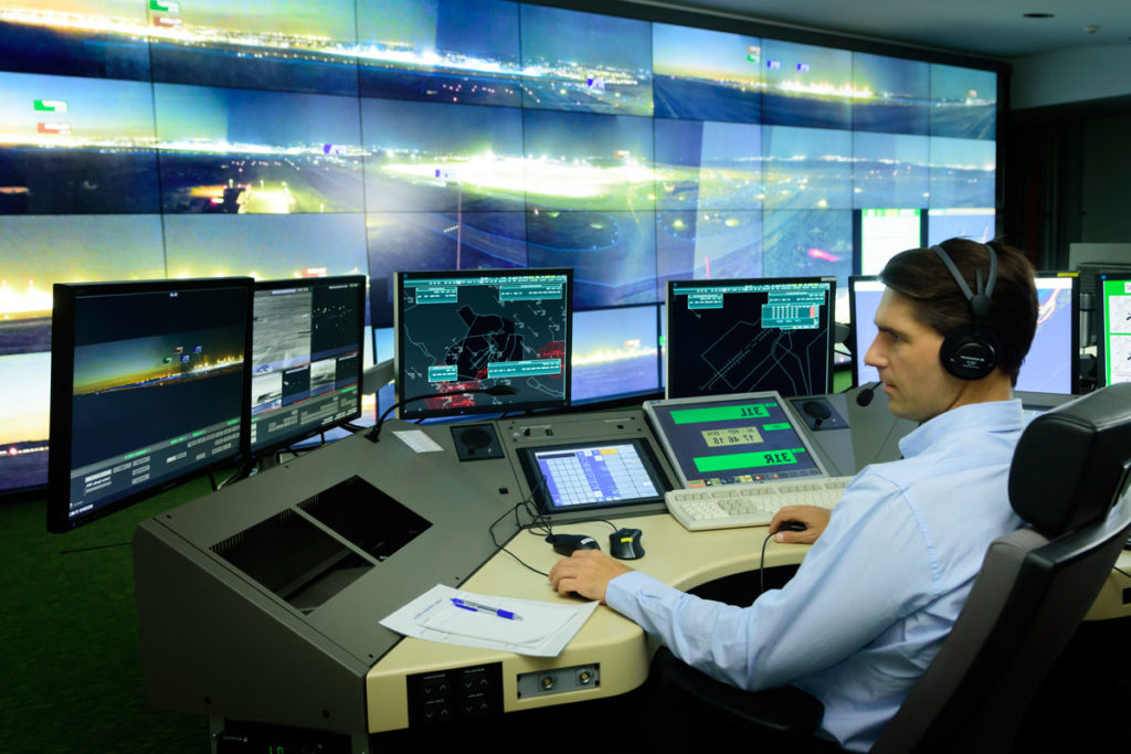 Air traffic Controller in remote tower in front of large screens