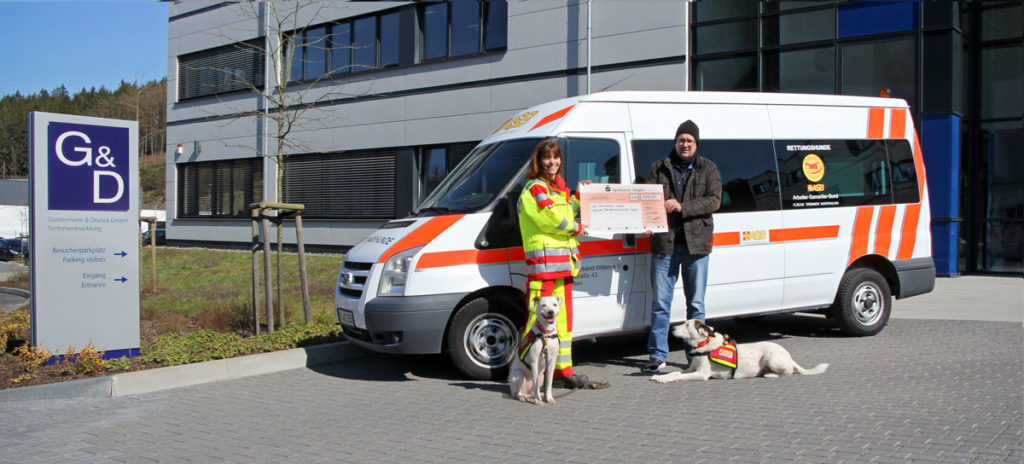Manuela Enders und Roland Ollek bei der Spendenübergabe mit Hunden und Einsatzfahrzeug