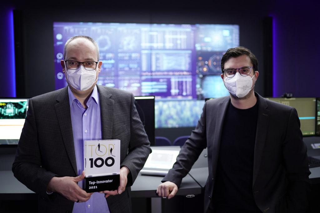 G&D CEOs Roland Ollek und Nils Strauch mit TOP-100-Award vor vielen Monitoren im ControlCenter-Xperience