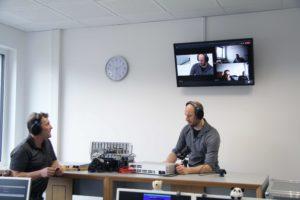 G&D Trainer sitzend an Arbeitsplätzen vor einer Videowand, über die die Teilnehmenden zugeschaltet sind.